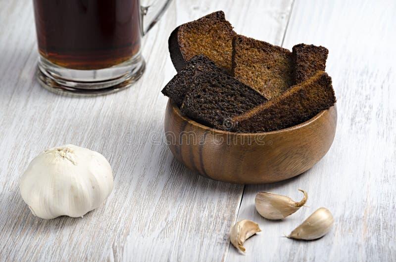 Två sorter av stekt bröd i en träplatta med vitlök och drinken i ett exponeringsglas på en träbakgrund royaltyfri foto