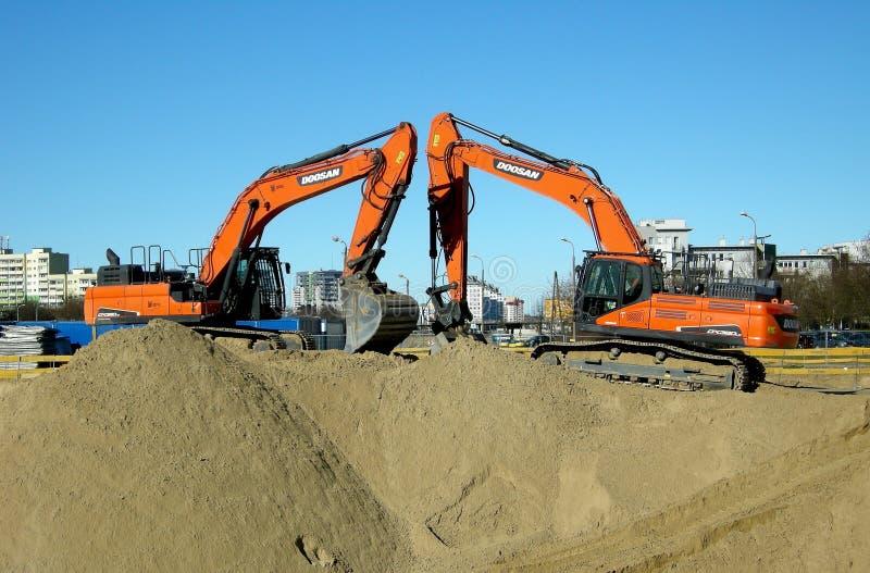 Två spårade orange grävskopor som förbereddes för arbete royaltyfri bild