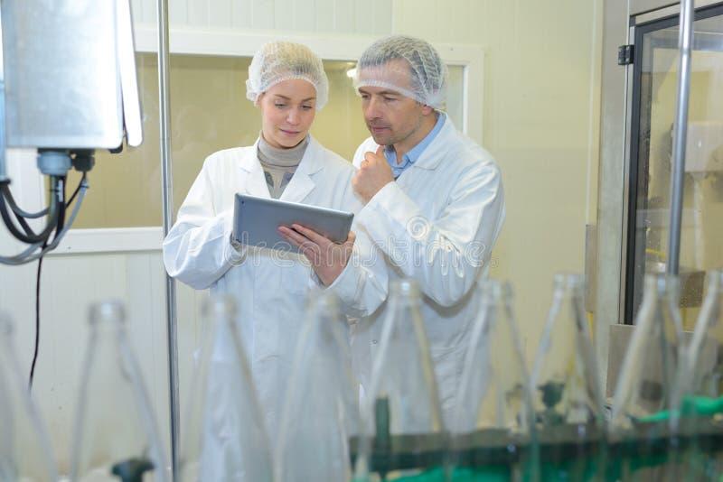 Två specialister i fabrik som kontrollerar flaskor royaltyfri foto