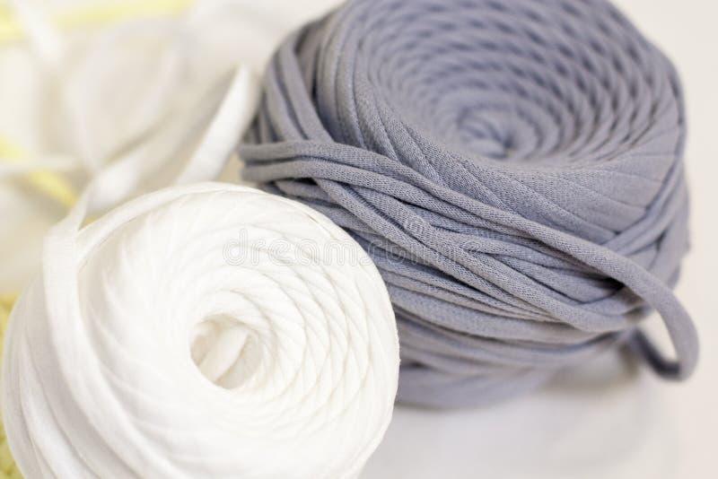 Två spolar av t-skjorta garn i vita och gråa färger arkivfoto