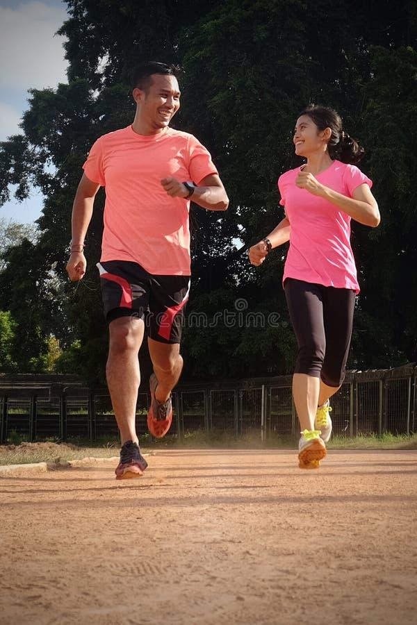 Tv? sportpartners joggar tillsammans p? en solig dag som b?r orange och rosa skjortor De ser de, och leendet, tycker om arkivbilder