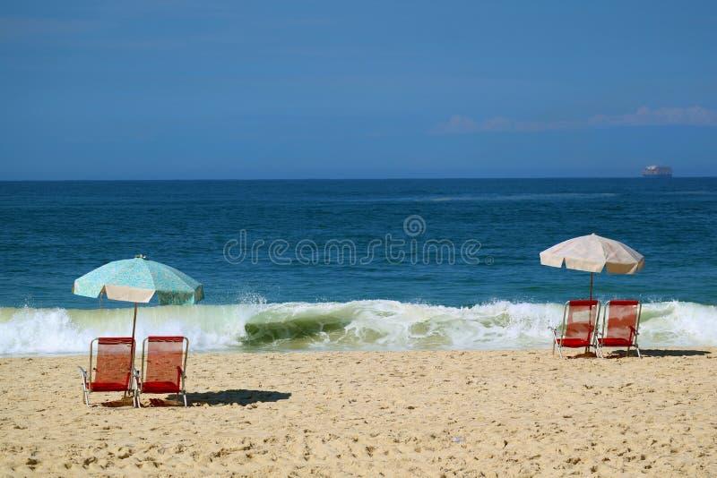 Tv? st?llde in av r?da strandstolar och en bl? strandslags solskydd p? den sandiga stranden som v?nder mot de krascha v?gorna och royaltyfri fotografi