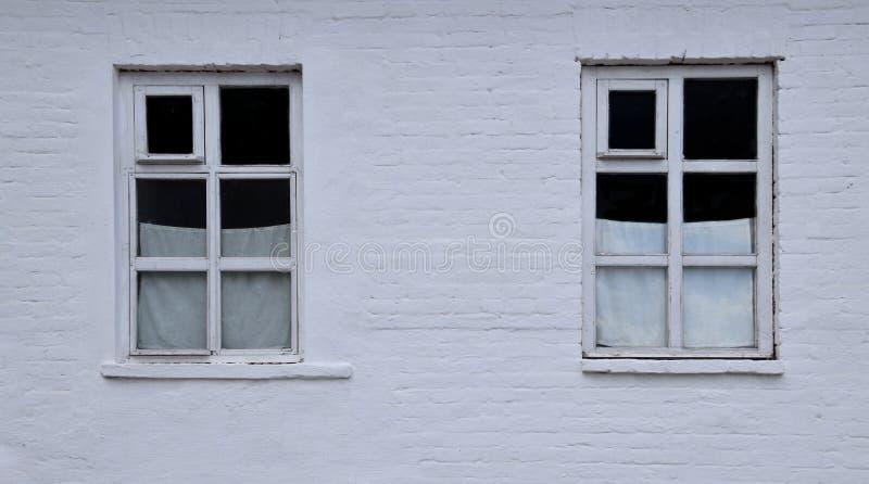 Två stadsfönster med vita gardiner arkivbilder
