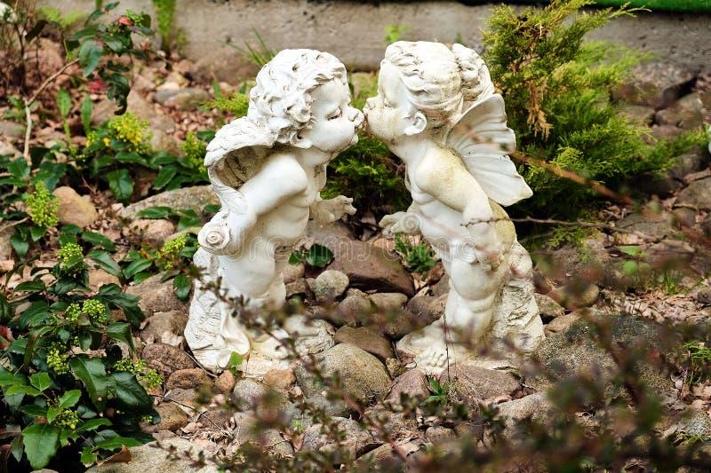 Två statyer av änglar i trädgården royaltyfri foto