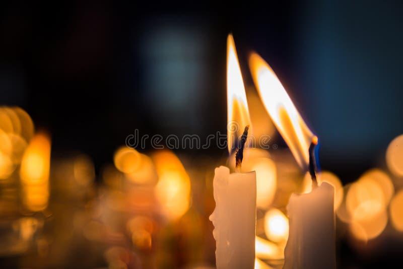 Två stearinljus flamma i en kyrklig tabell arkivbilder