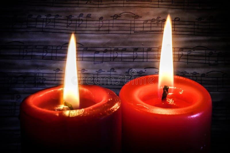 Två stearinljus och musikanmärkningar arkivfoto