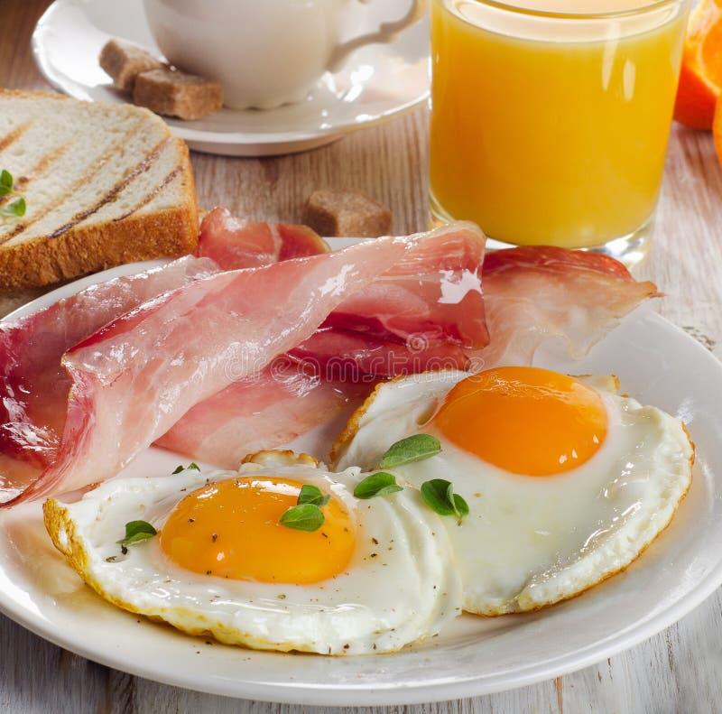 Två stekte ägg, bacon, rostade bröd, fruktsaft och kaffe royaltyfri fotografi