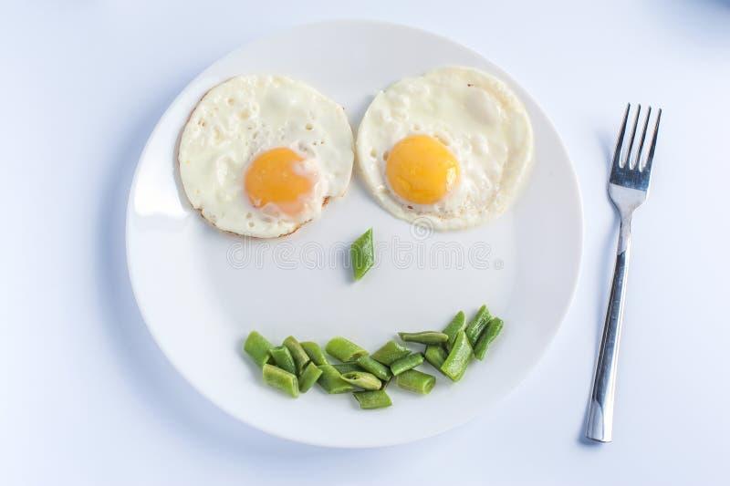 Två stekte ägg med haricot vert på den vita plattan, gaffel på ljus bakgrund fotografering för bildbyråer
