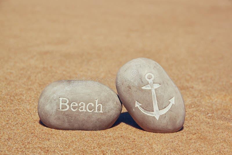 Två stenkiselstenar med ordet sätter på land och ankrar undertecknar över den sandiga stranden arkivfoton