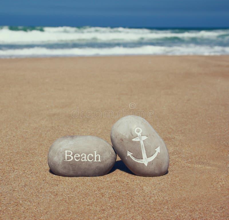 Två stenkiselstenar med ordet sätter på land och ankrar undertecknar över den sandiga stranden och havshorisonten arkivbild