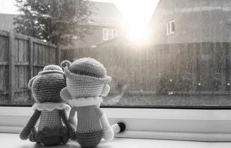 Två sticka dockor pojke och flickainnehavet räcker sammanträde bredvid fönstret, svartvit färg royaltyfri bild