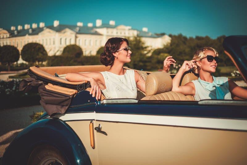 Två stilfulla damer i en klassikercabriolet arkivfoto