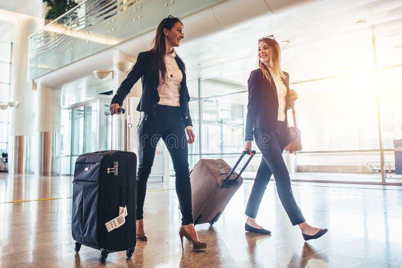 Två stilfulla kvinnliga handelsresande som går med deras bagage i flygplats royaltyfri foto