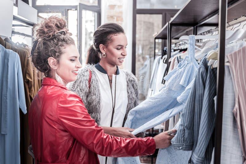 Två stilfulla kvinnor som kommer till den nya shoppinggallerian som ser trevliga klänningar royaltyfria foton