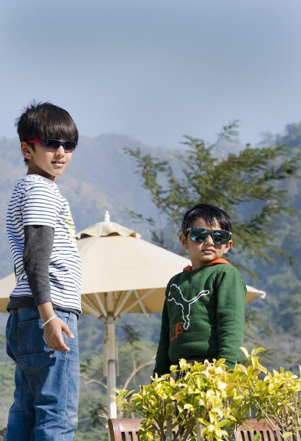 Två stilfulla ungar som har gyckel arkivbild