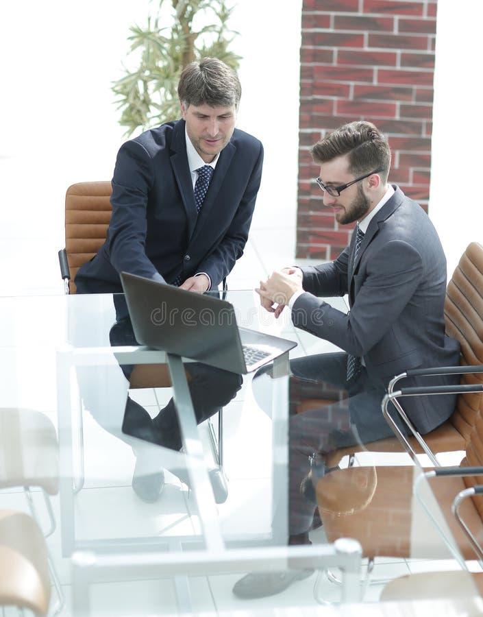 Två stiliga affärsmän som diskuterar avtalet i modernt konferensrum royaltyfri bild