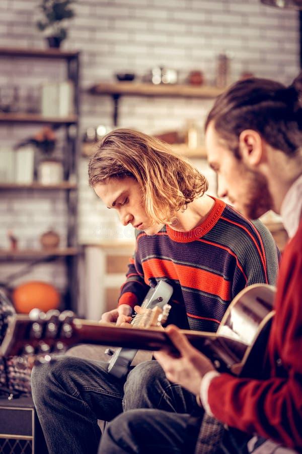 Två stiliga begåvade unga män som känner sig bra spela gitarren royaltyfri foto