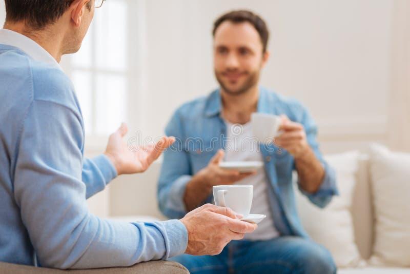 Två stiliga lyckliga män som dricker kaffe arkivbild