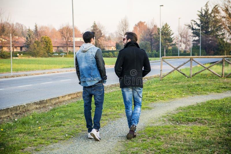 Två stiliga unga män, vänner, i en parkera arkivfoton