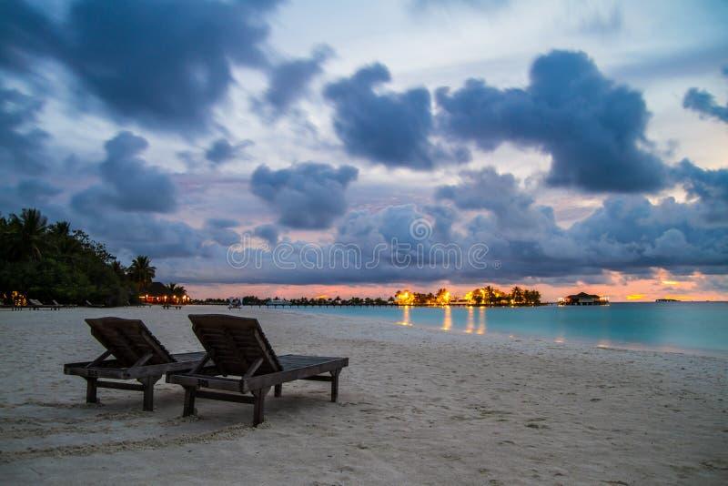Två stolar på den maldiviska stranden på den härliga solnedgången fotografering för bildbyråer