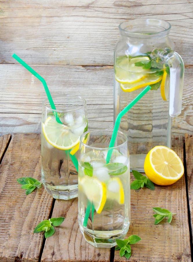 Två stora exponeringsglas av kall lemonad med is, citron, mintkaramellsidor royaltyfria foton