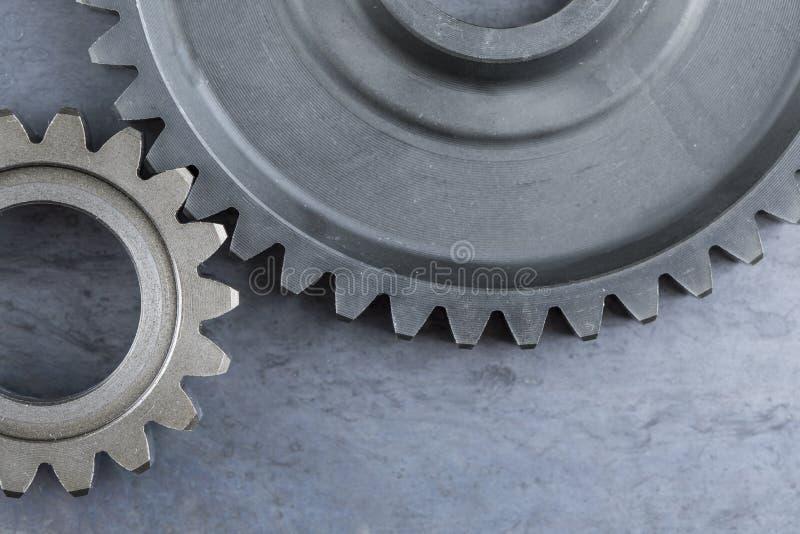 Två stora gripa in i varandra kugghjul på s-stålarket fotografering för bildbyråer