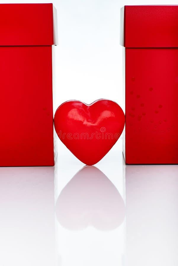 Två stora röda gåvaaskar och röd vaxhjärta arkivbilder