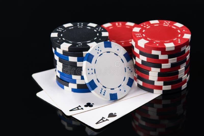 Två stora spela kort med pokerchiper på en mörk bakgrund royaltyfria bilder