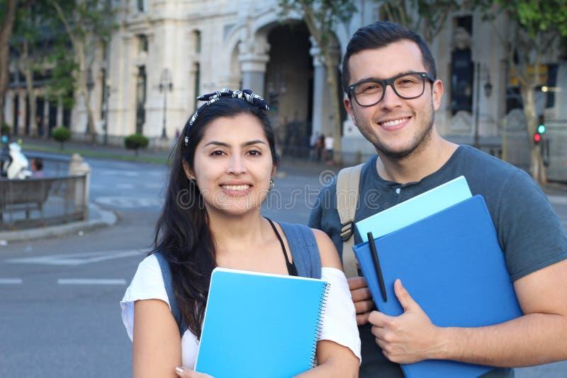 Två studenter för blandat lopp som utomhus ler arkivbild