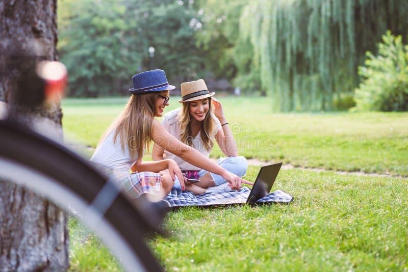 Två studenter för unga kvinnor parkerar in sammanträde på gräs som talar, genom att använda bärbara datorn arkivfoto