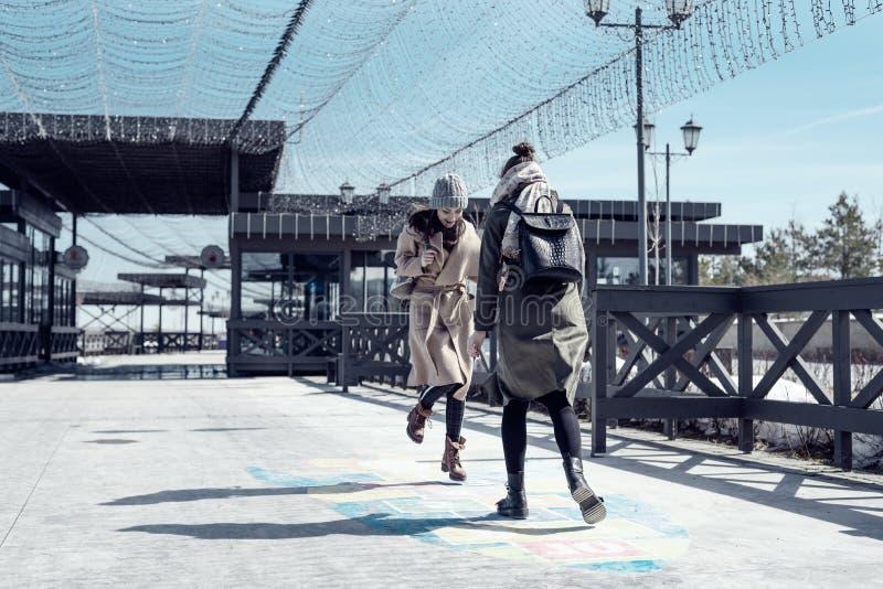 Två studenter går på gatan och hoppar hage på asfalten, ungdom, barndom arkivfoto