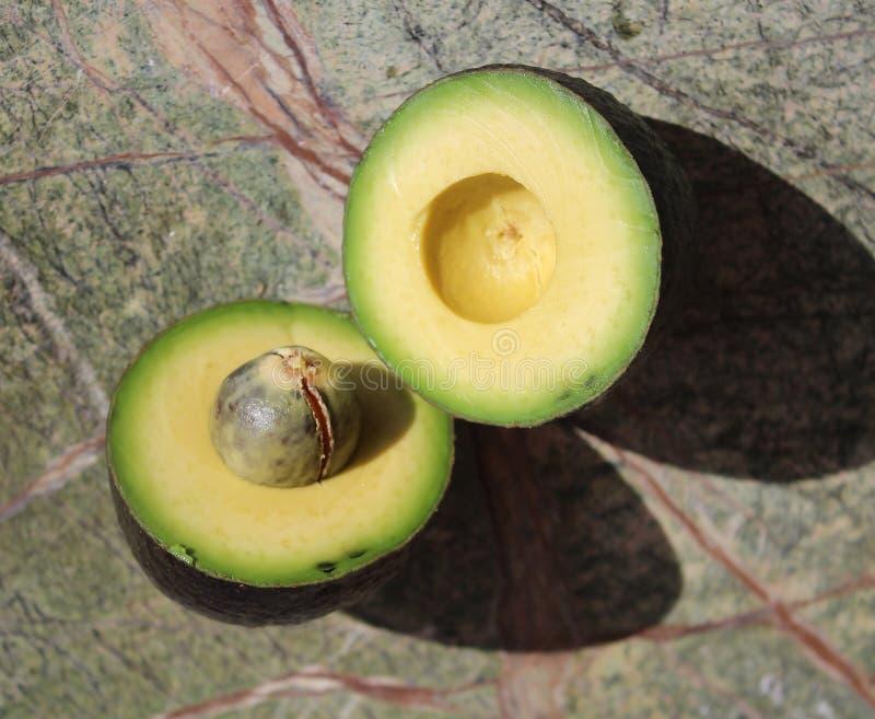 Två stycken av avokadot Avokadosnitt in i två delar arkivbilder
