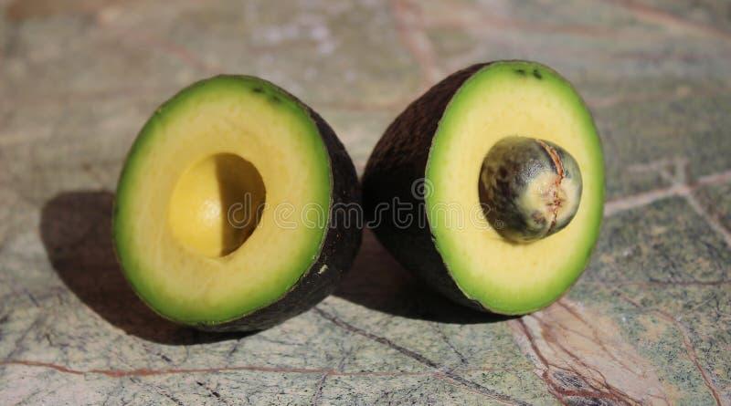 Två stycken av avokadot Avokadosnitt in i två delar arkivfoto