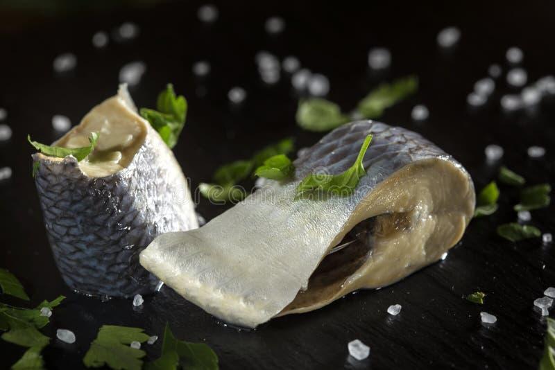 Två stycken av den marinerade sillfisken med salt kritiserar på arkivbild