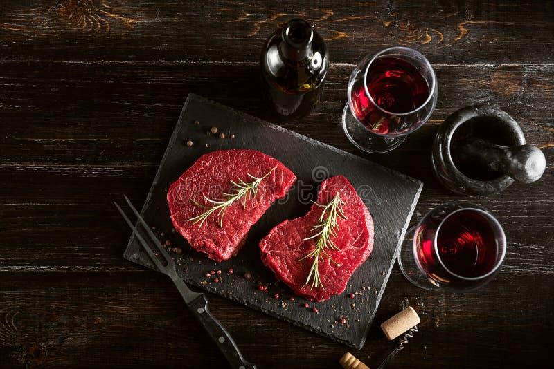 Två stycken av nytt kött som förbereds för att steka och vin med exponeringsglas på en trätabell royaltyfri fotografi
