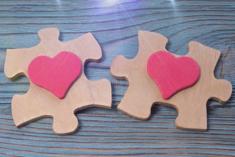 Två stycken av pussel, två stycken av hjärta på en träbakgrund royaltyfri bild