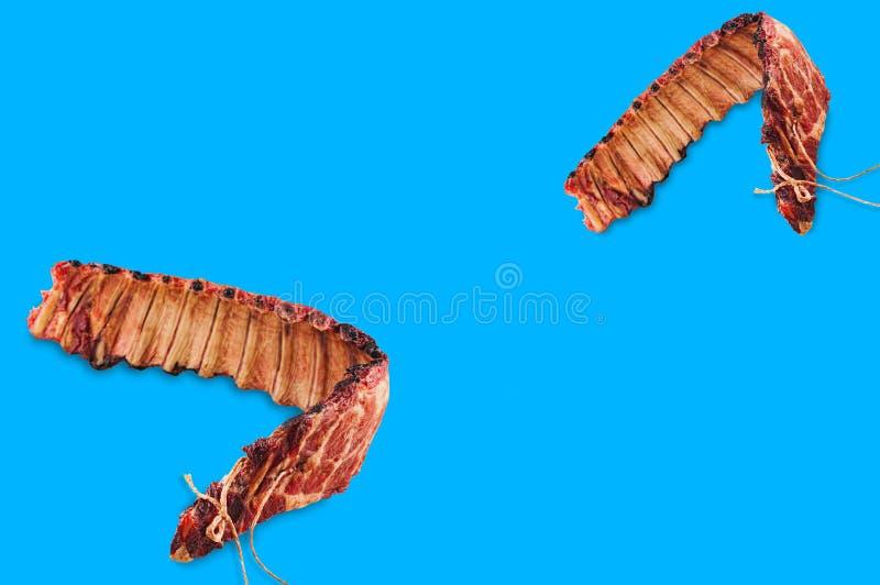 Två stycken av rökte stöd av griskött på blå bakgrund royaltyfria bilder