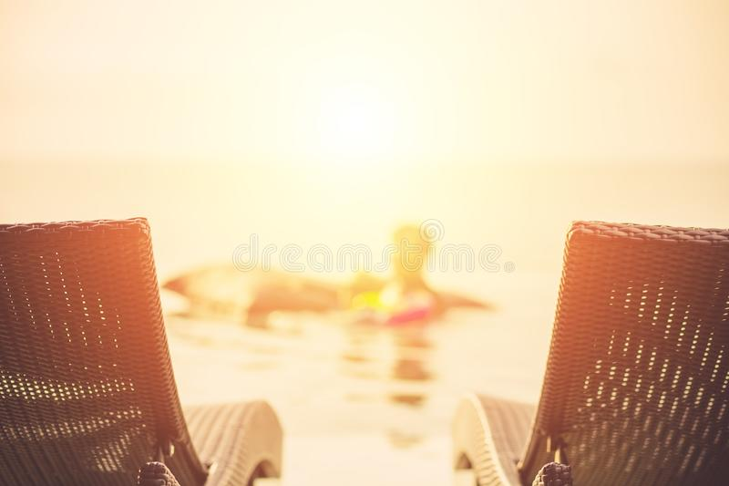 Två sunbeds i härlig simbassäng för lyxigt hotell med solnedgångplatsbakgrund och folk som spelar i simbassängen royaltyfri foto