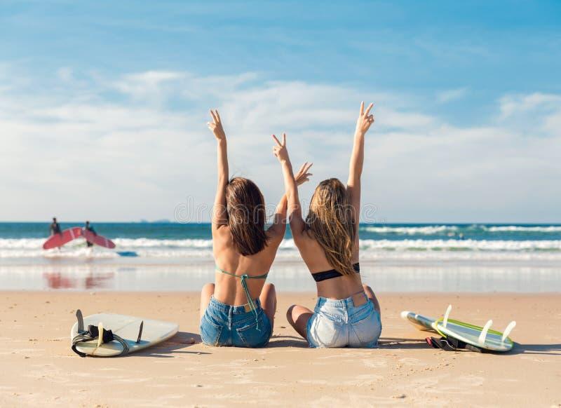 Två surfareflickor på stranden arkivfoto