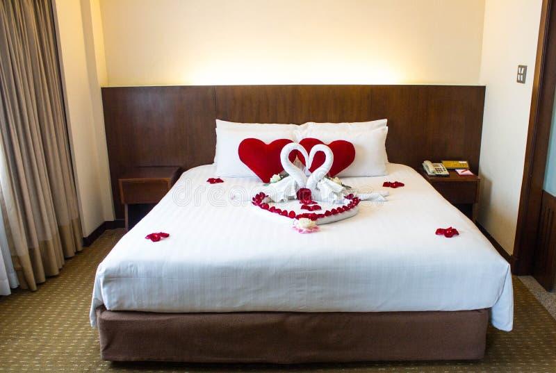 Två svanar som göras från handdukar, är kyssande på vit säng för bröllopsresa arkivfoton