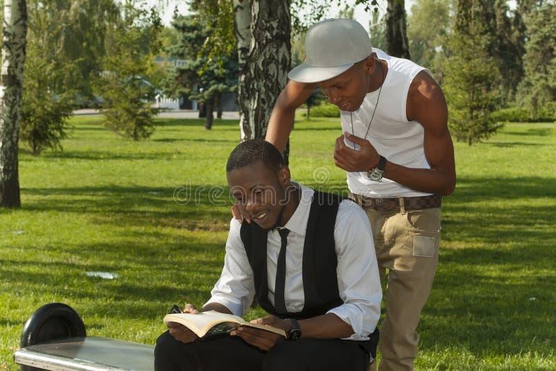 Två svart deltagare som läser en boka arkivfoto