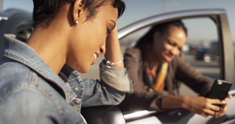 Två svart kvinnavänner som smsar på mobiltelefonen och lutande agains fotografering för bildbyråer