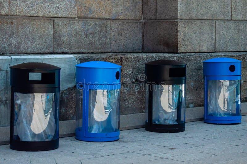 Två svarta avskrädefack och två blått att återanvända fack Offentlig avfallavfalls på burk royaltyfri bild