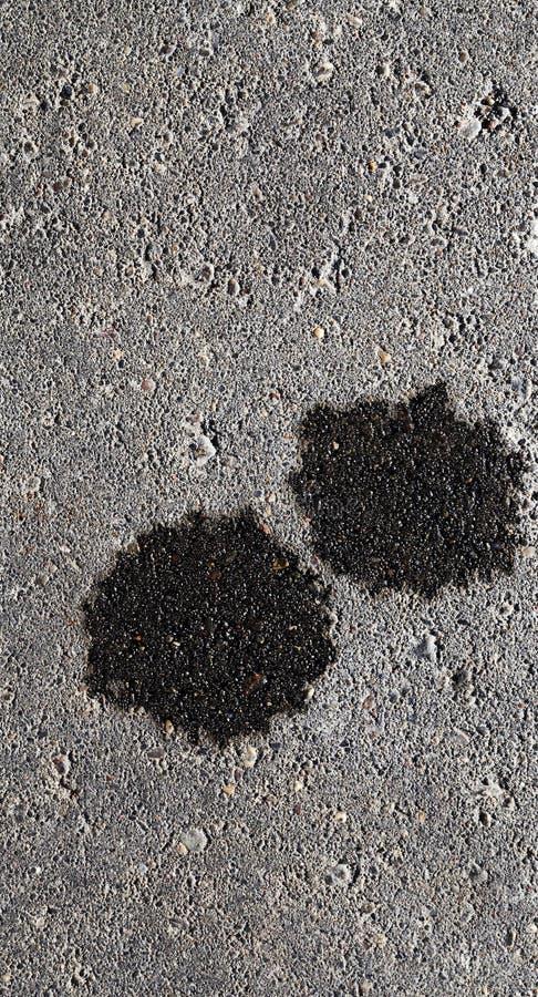 Två svarta fläckar av motorolja arkivfoton