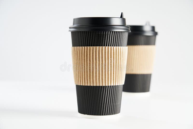 Två svarta kopp för pappers- disponibelt kaffe för tagande bort eller att gå som isoleras på vitt, utrymme för designorientering royaltyfria foton