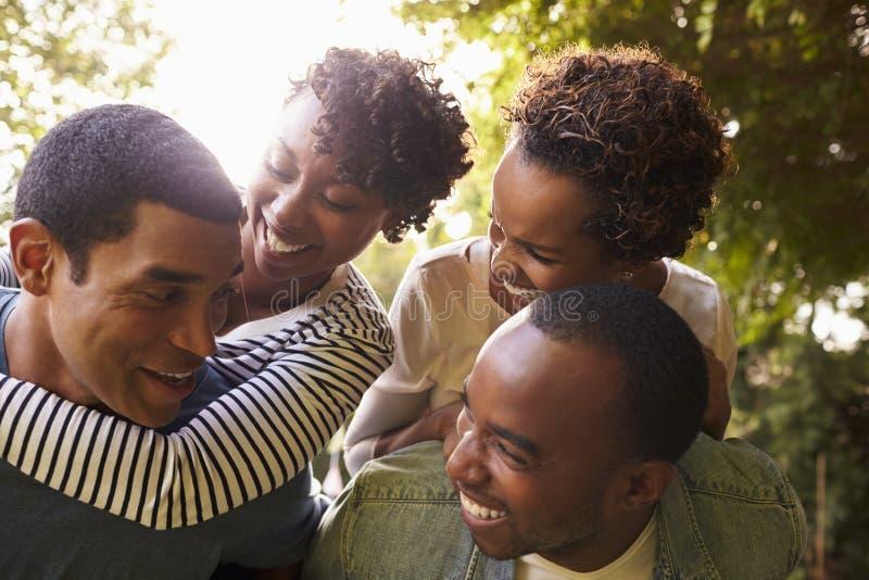 Två svarta par för vuxen människa har rolig piggybacking, nära övre royaltyfria bilder