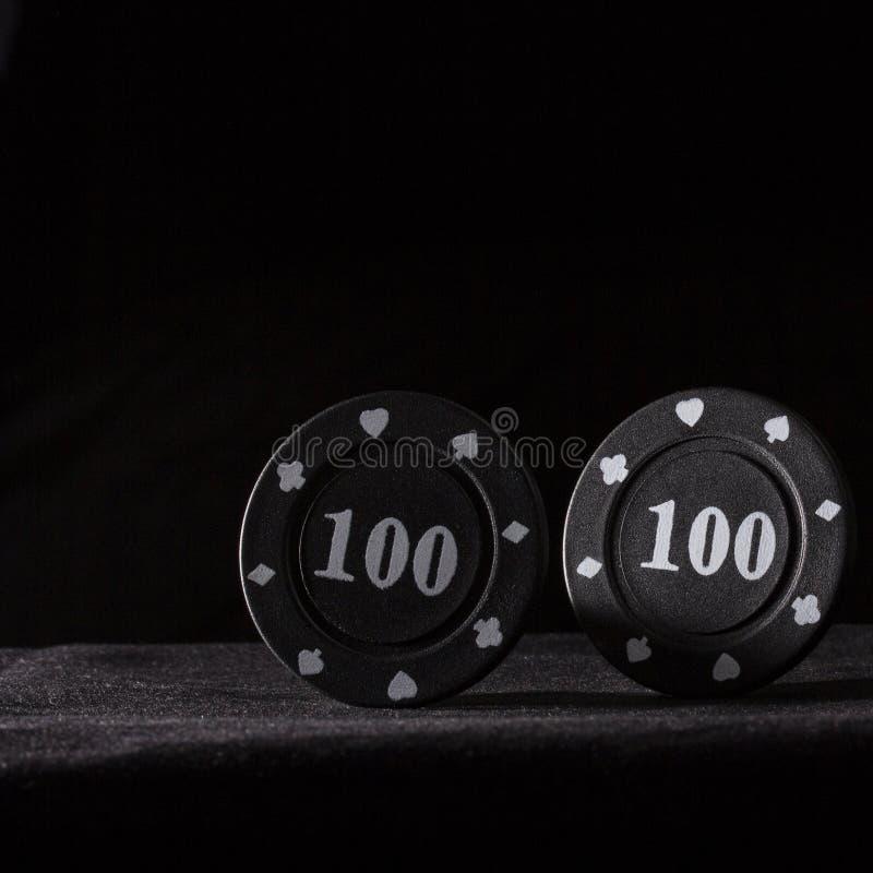 Två svarta pokerchiper på en mörk bakgrund royaltyfri foto