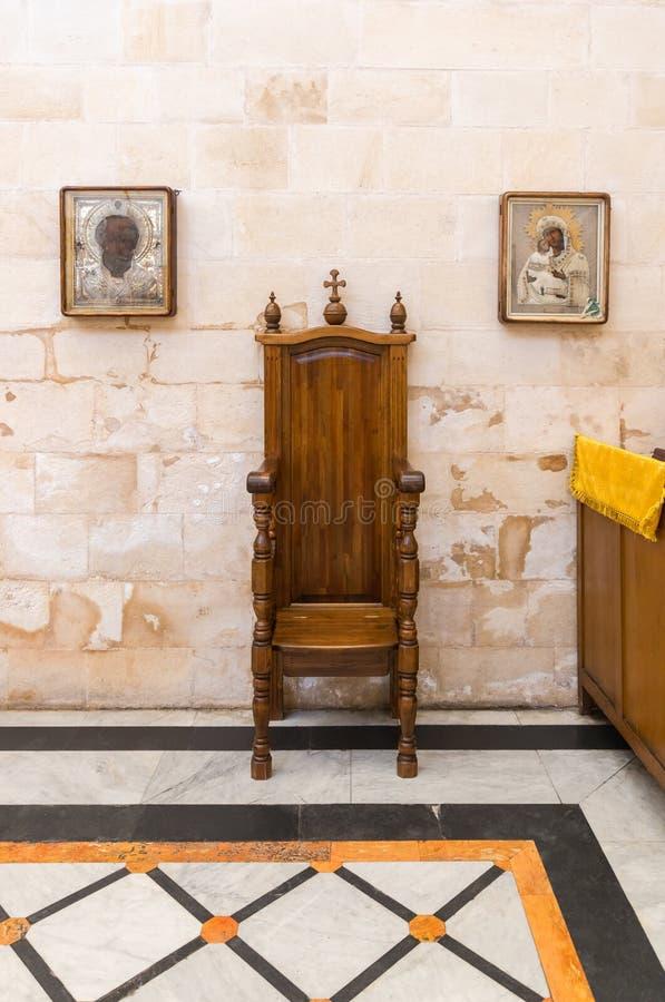 Två symboler hänger på väggen på sidorna av den dekorativa träbiskopsstolen i den Alexander Nevsky kyrkan i Jerusalem, Israel arkivfoto