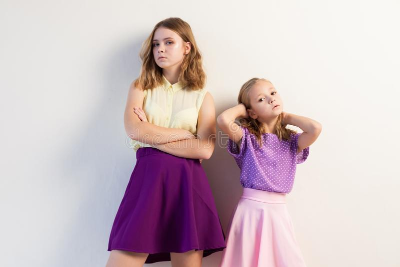 Två systerflickor i kulöra väggar för klänningvit royaltyfri foto