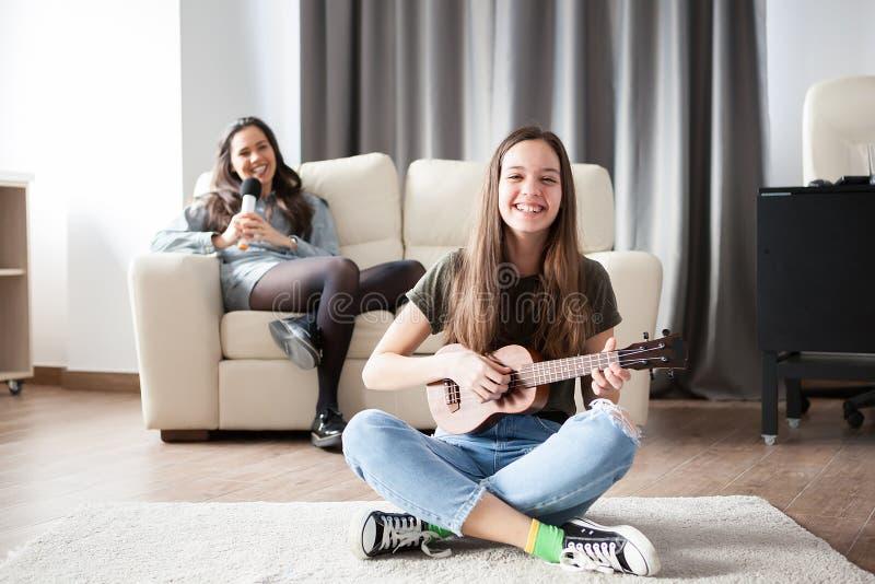 Två systrar, den mer unga spelar en liten gitarr på annat är framme sjungande i baksidan royaltyfri fotografi
